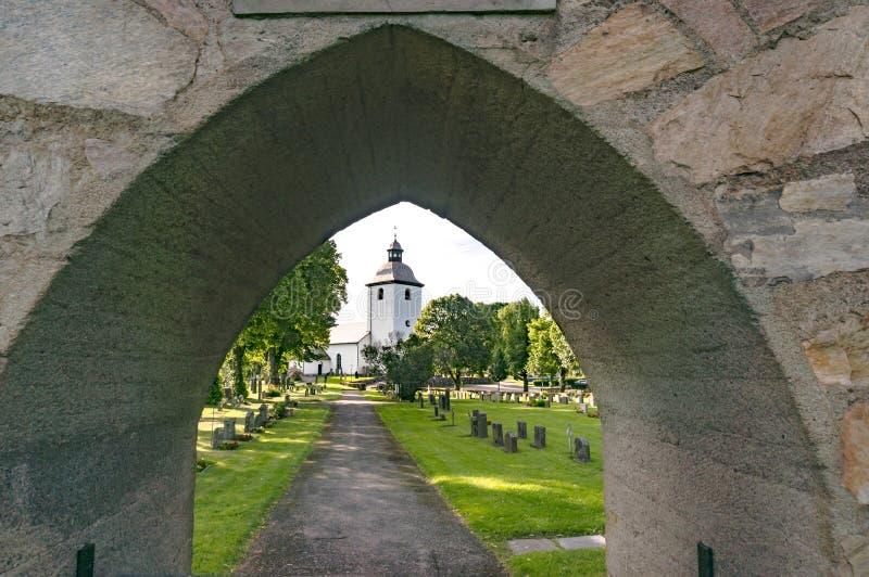 Vista de un cementerio y de una iglesia viejos debajo del arco foto de archivo
