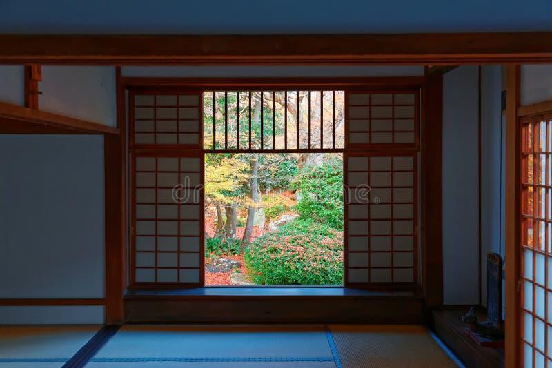 Vista de un jardín japonés del patio a través del shoji de desplazamiento de las puertas de malla de un cuarto en Genko-an foto de archivo
