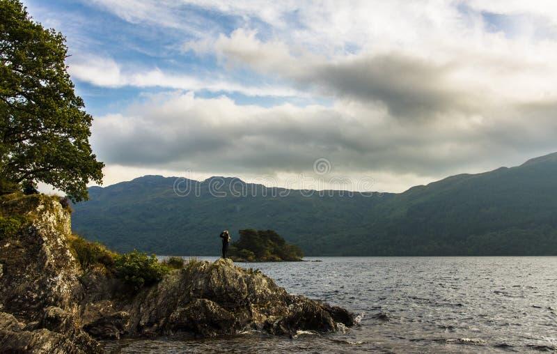 Vista de un lago con una muchacha imagen de archivo libre de regalías
