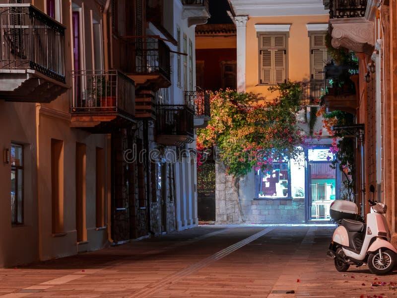 Vista de un streetin Nafplio, Grecia, en la noche adornada por las flores y vides y vespa parqueada fotos de archivo