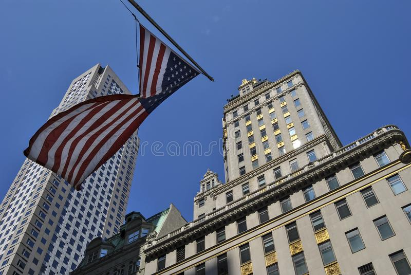 Vista de una bandera americana y de los rascacielos altos en Manhattan, New York City foto de archivo