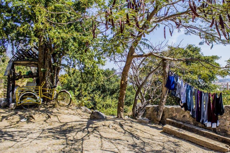 Vista de una bicicleta abandonada amarilla de la carga en una porción árida con el colgante azul de la ropa fotos de archivo