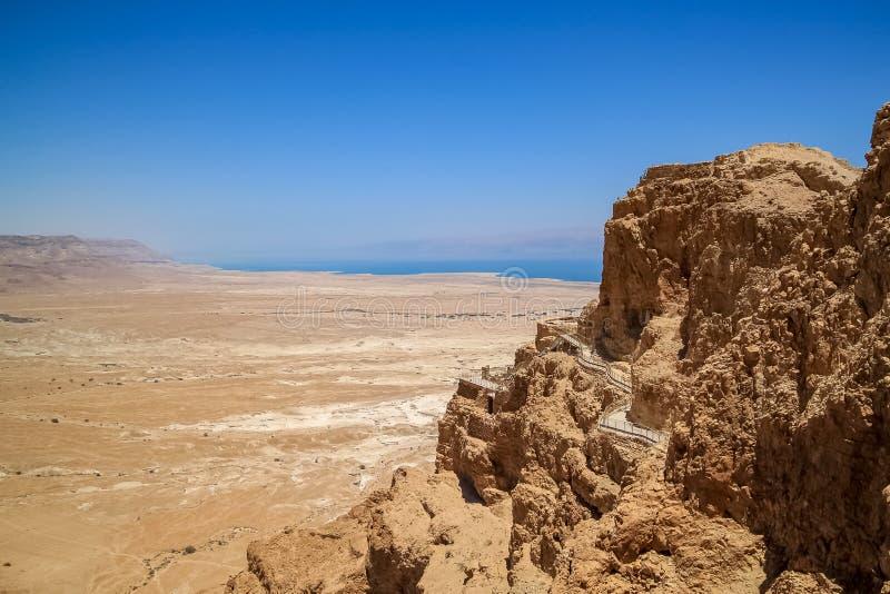 Vista de una calzada peatonal encima del lado de la montaña de Masada, con el mar muerto en fondo nebuloso fotografía de archivo