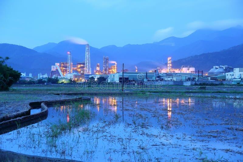 Vista de una fábrica en el medio de tierras de labrantío con las chimeneas que emiten humo en la madrugada foto de archivo