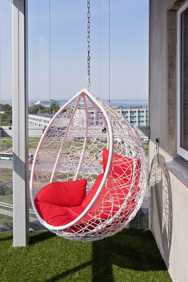 Vista de una silla colgante acogedora moderna con las almohadas rojas en un balcón fotos de archivo libres de regalías