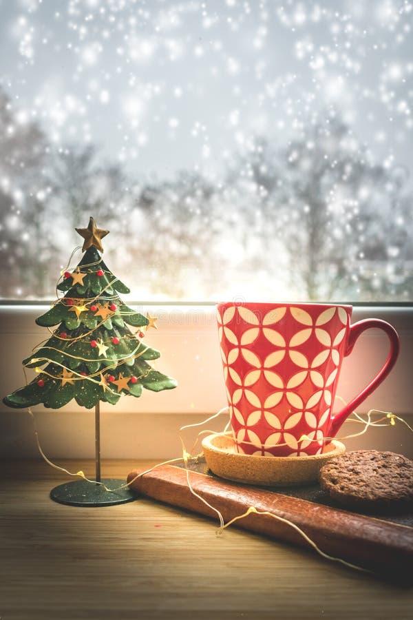 Vista de una taza de café y de una decoración rojas de la Navidad en una ventana con el fondo nevoso fotos de archivo libres de regalías