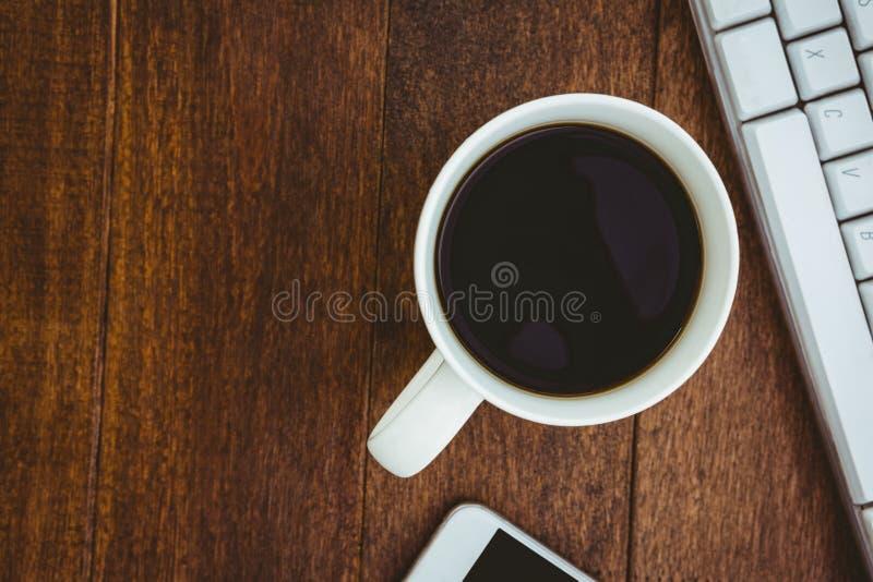 Vista de una taza de café y de un teclado imagen de archivo