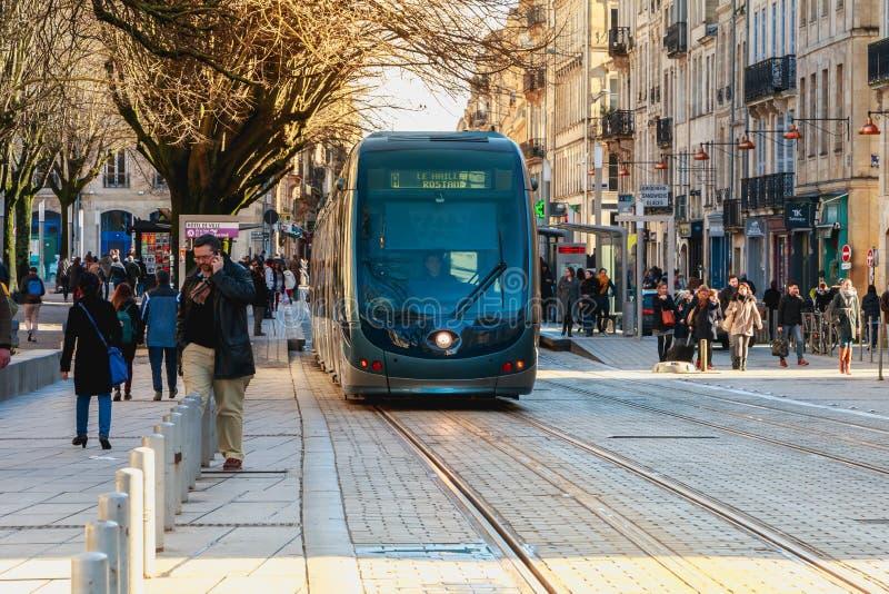 Vista de una tranvía que corre entre transeúntes en una calle de la ciudad fotografía de archivo