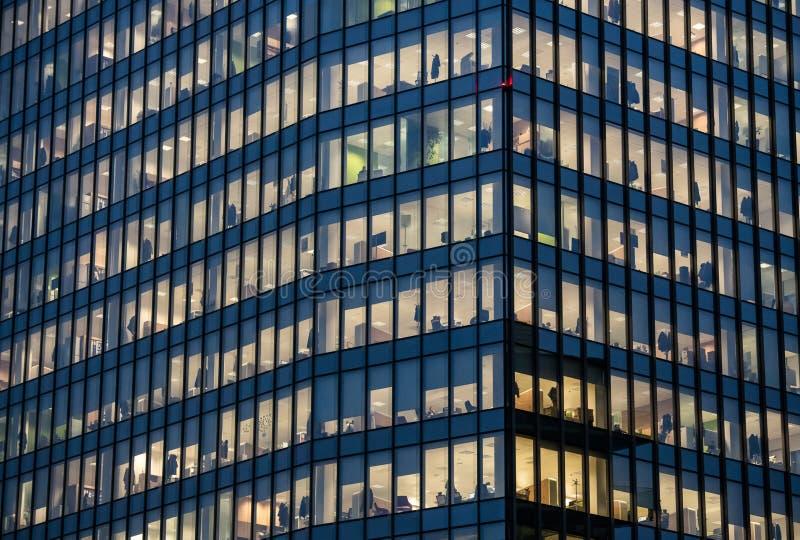 Vista de ventanas con la gente que trabaja dentro de un edificio de oficinas en la noche en Milán, Italia imágenes de archivo libres de regalías