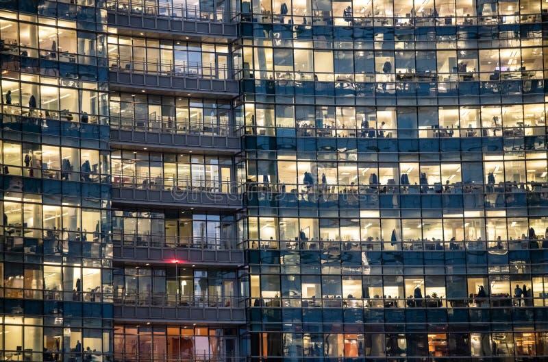 Vista de ventanas iluminadas con la gente que trabaja dentro de un edificio de oficinas bancario en la noche en Milán, Italia fotos de archivo libres de regalías
