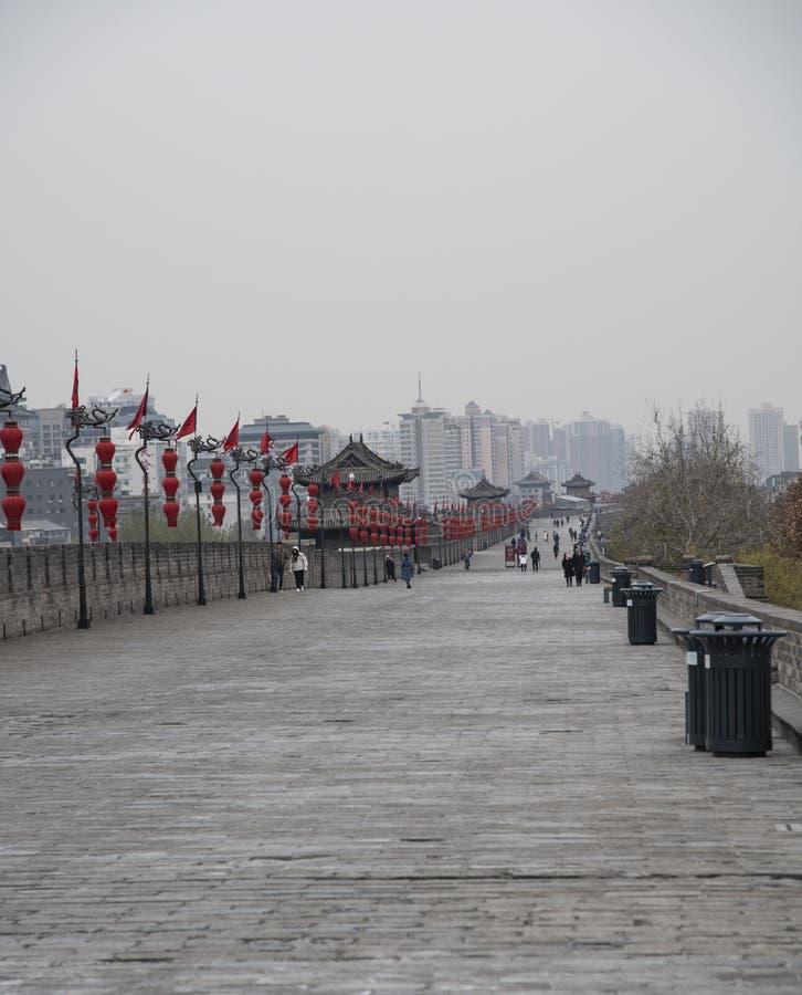 Vista dei bastioni di Xian City Wall e strada pedonale con le insegne ed i pali di bandiera rossi - Imagen fotografia stock libera da diritti
