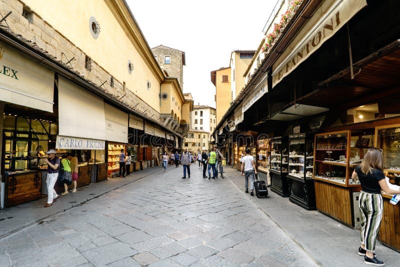 : Vista dei commerci situati ai lati del ponte sul Arno, chiamati ` di Ponte Vecchio del ` con la camminata della gente immagini stock libere da diritti