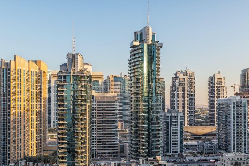 Vista dei grattacieli con cielo blu ed il sole che riflettono sulla finestra Con la luce di tramonto I UAE fotografie stock libere da diritti