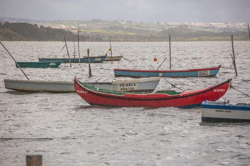 Vista dei pescherecci tradizionali che galleggiano sull'orlo della laguna, del forte vento e della pioggia di Nazare, nel Portoga fotografie stock