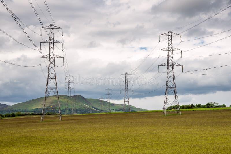 Vista dei piloni di elettricità in un paesaggio rurale fotografie stock
