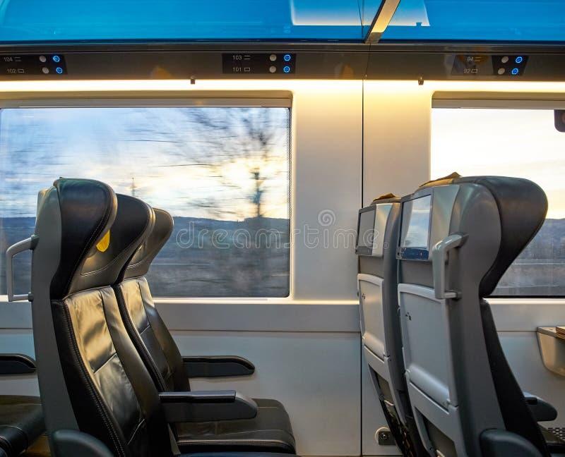 Vista dei sedili che conducono treno con paesaggio fuori della finestra Schermi e viaggio comodo fotografia stock