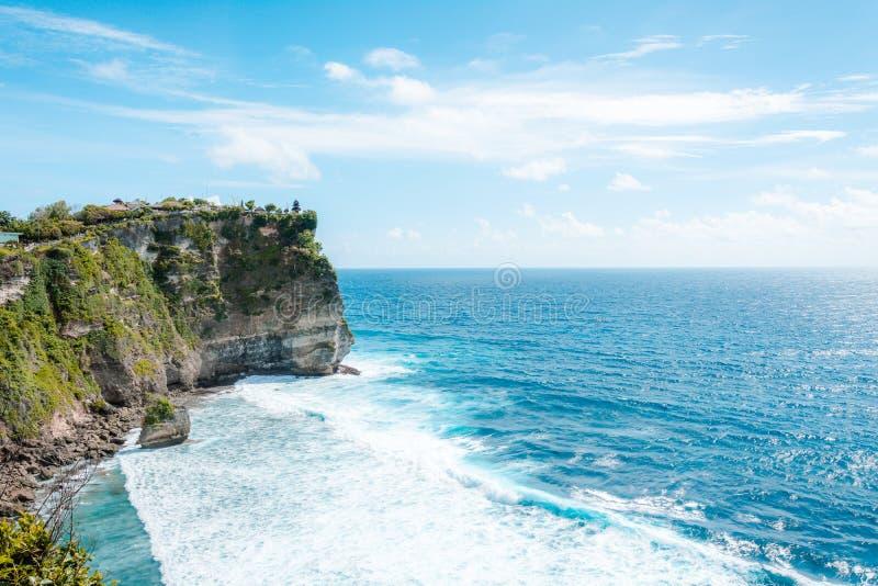 Vista del acantilado con las ondas en el mar del templo hindú Pura Luhur Uluwatu imagenes de archivo