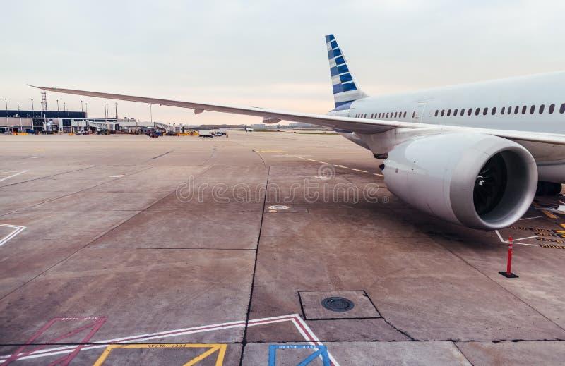 Vista del ala y del motor del aeroplano en la pista de despeque en el aeropuerto foto de archivo