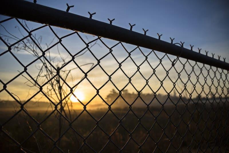 Vista del amanecer de detrás una cerca fotografía de archivo libre de regalías