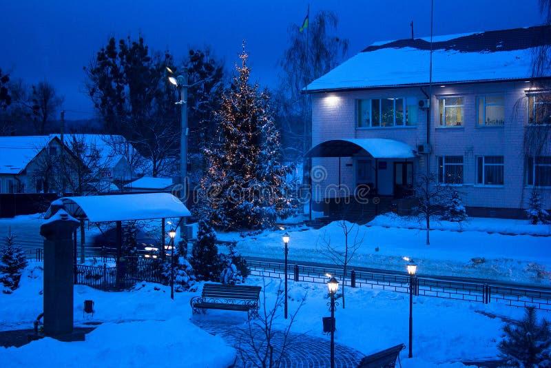 Vista del banco contro l'albero di Natale e della lanterna brillante con nevicare Tono blu Colpo di notte fotografie stock