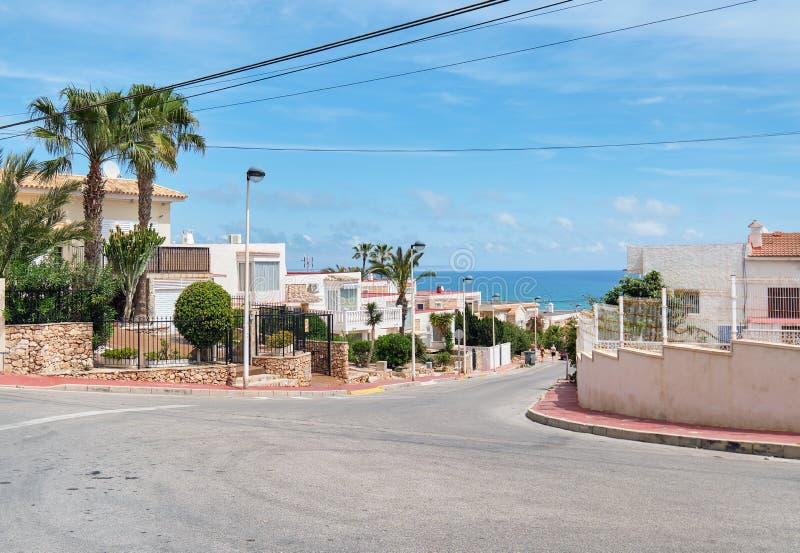 Vista del bordo della strada alla strada vuota che conduce al mar Mediterraneo, case residenziali delle ville costiere di estate, fotografia stock