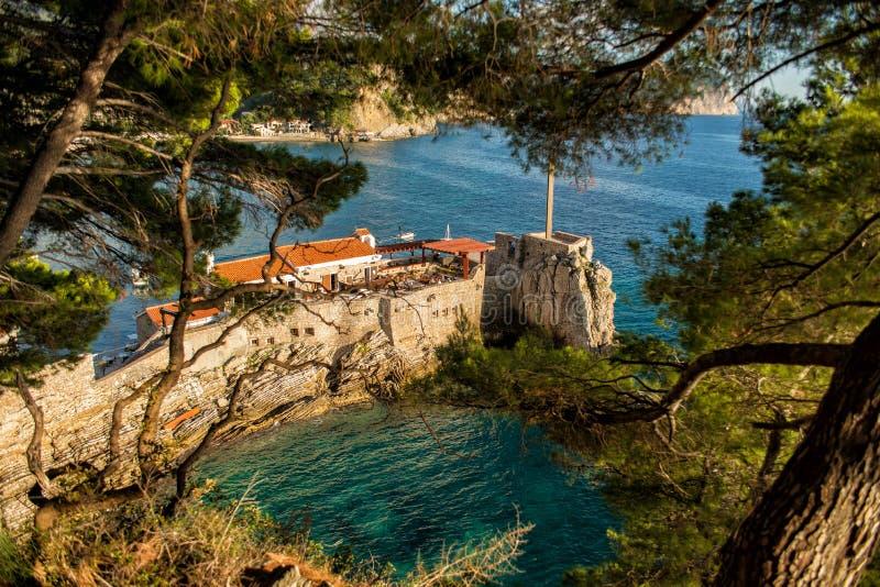 Vista del cabo rocoso en la ciudad de vacaciones de Petrovac Paisaje mediterráneo hermoso en el día soleado, Montenegro imagen de archivo
