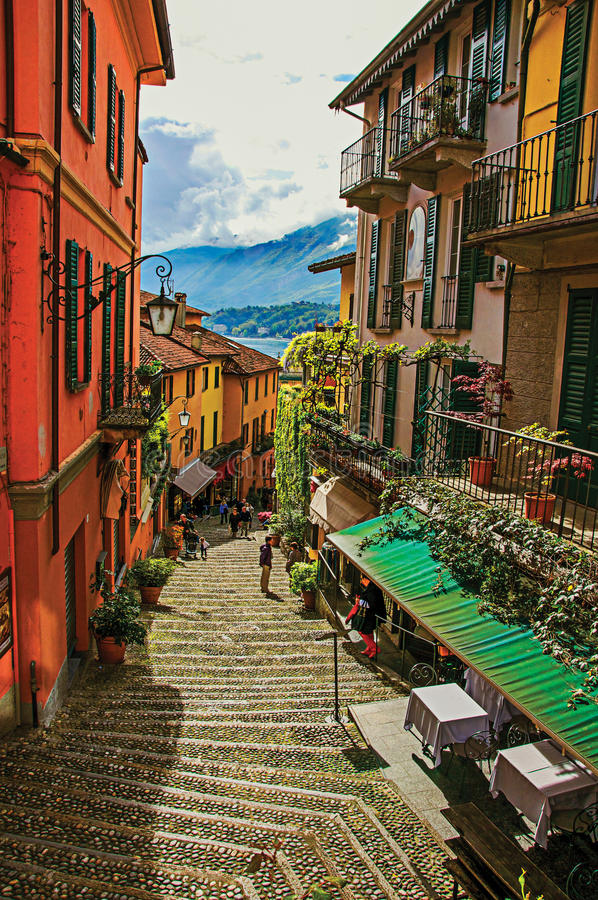 Vista del callejón en ladera, de edificios con la enredadera y del lago Como en Bellagio fotografía de archivo