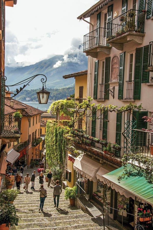 Vista del callejón en ladera, de edificios con la enredadera y del lago Como en Bellagio imágenes de archivo libres de regalías