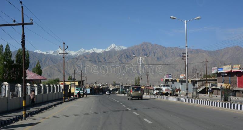Vista del camino de la montaña con el pequeño pueblo en Leh, la India fotos de archivo