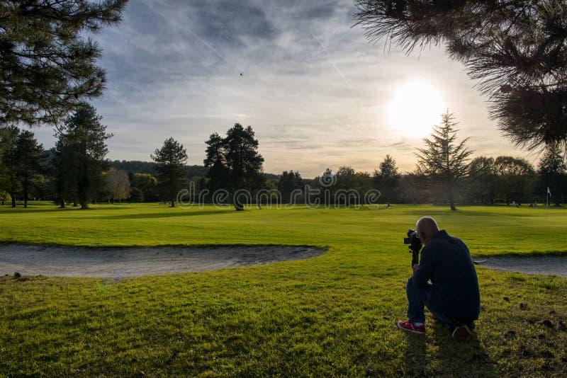Vista del campo da golf verde con il fotografo fotografia stock libera da diritti
