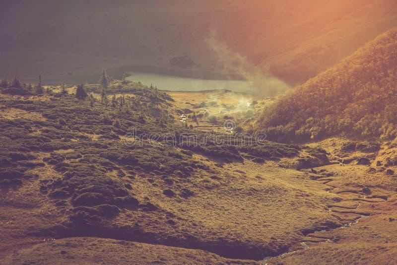 Vista del campo del lago e del turista della montagna vicino lui fotografie stock libere da diritti