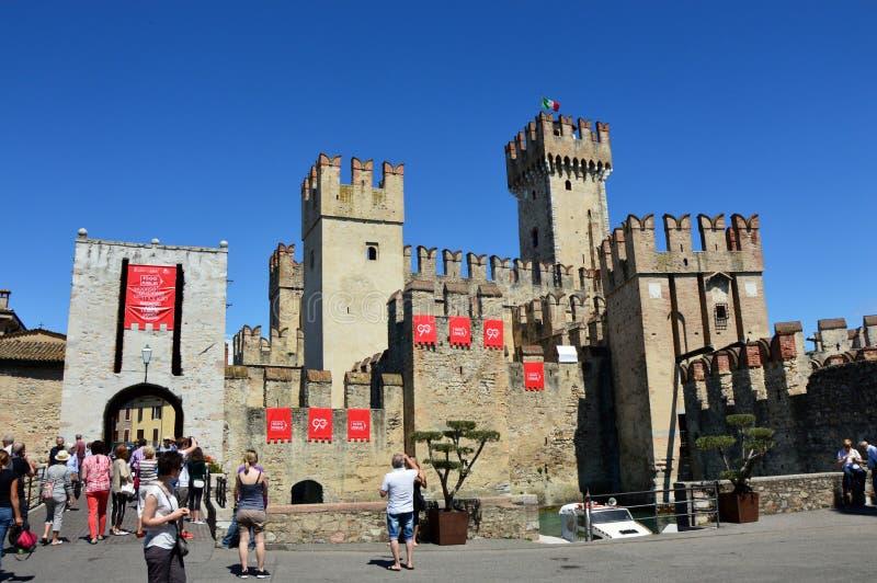 Vista del castillo medieval de Scaliger de Sirmione con el letrero de la reunión italiana Mille Miglia y de la lancha de carreras foto de archivo