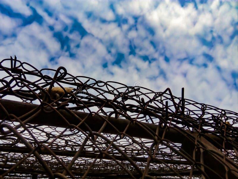 Vista del cielo con las nubes debido al alambre de púas fotografía de archivo