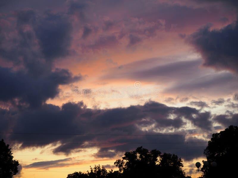 Vista del cielo drammatico sopra il sity al tramonto con le nuvole blu scuro fotografia stock