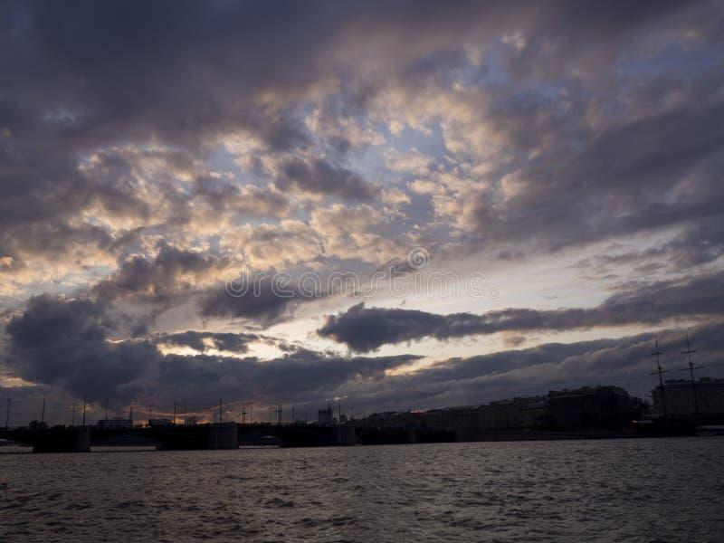 Vista del cielo drammatico sopra il sity al tramonto con le nuvole blu scuro fotografie stock libere da diritti