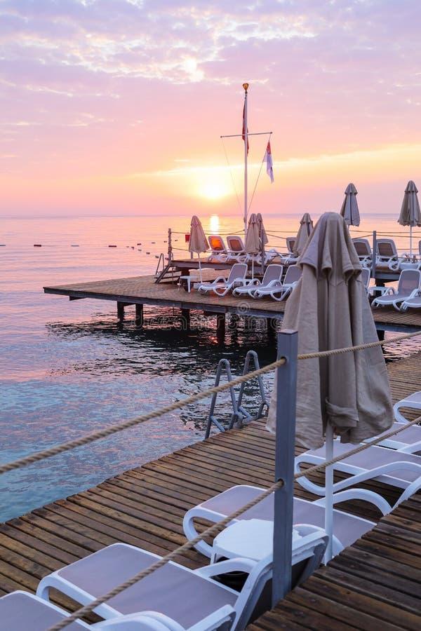 Vista del cielo, del mar y de la plataforma románticos de la salida del sol con los ociosos y los paraguas vacíos del sol imagen de archivo