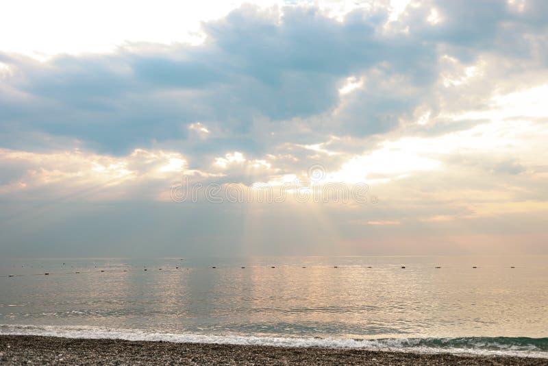 Vista del cielo maravilloso con las nubes y haces y mar majestuosos del sol Paisaje marino en amanecer fotos de archivo