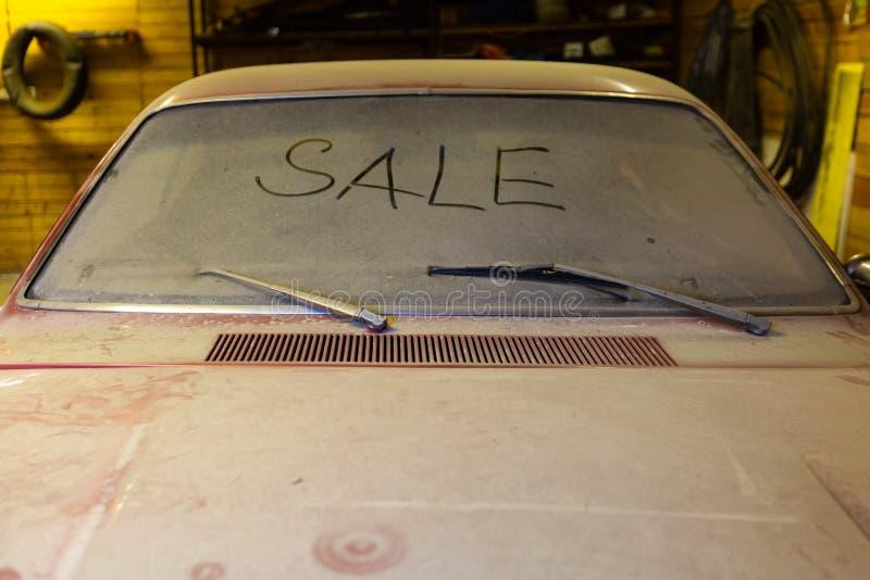 Vista del coche viejo en garaje con la pantalla sucia del viento de la capilla polvorienta con VENTA del título por el finger y e fotografía de archivo