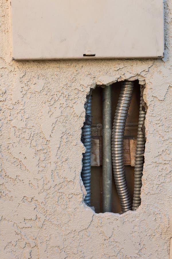 Vista del condotto elettrico vista attraverso un foro nello stucco esteriore di una casa che conduce alla scatola del pannello immagini stock