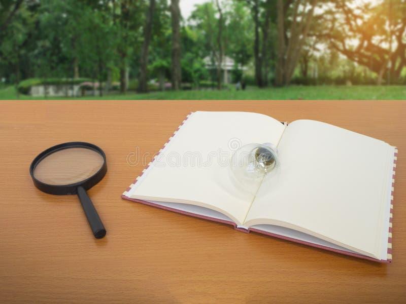 Vista del cuaderno y de la lupa de la bombilla en la tabla de madera con el fondo verde del árbol imagen de archivo