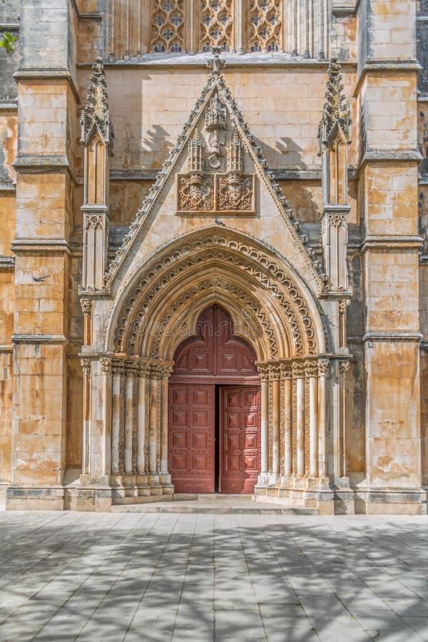 Vista del dettaglio al portone ed alla porta frontali della facciata esteriore gotica decorata del monastero di Batalha, Mosteiro immagine stock libera da diritti
