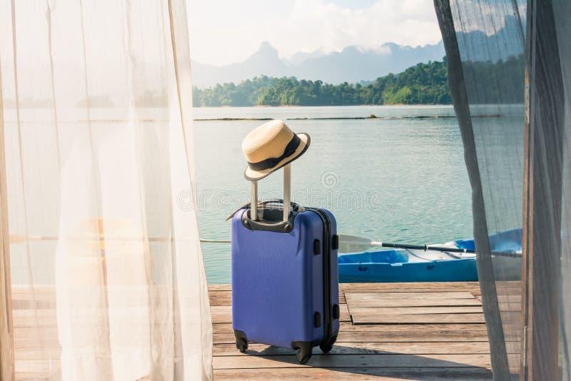 Vista del dormitorio con la cortina de ventana y la maleta del viaje con el sombrero fotografía de archivo