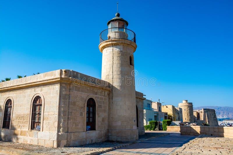 Vista del faro y del fuerte en Roquetas de marcha foto de archivo