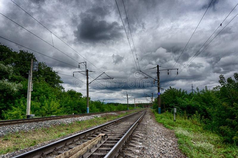 Vista del ferrocarril que retrocede en la distancia a través de los árboles fotografía de archivo libre de regalías