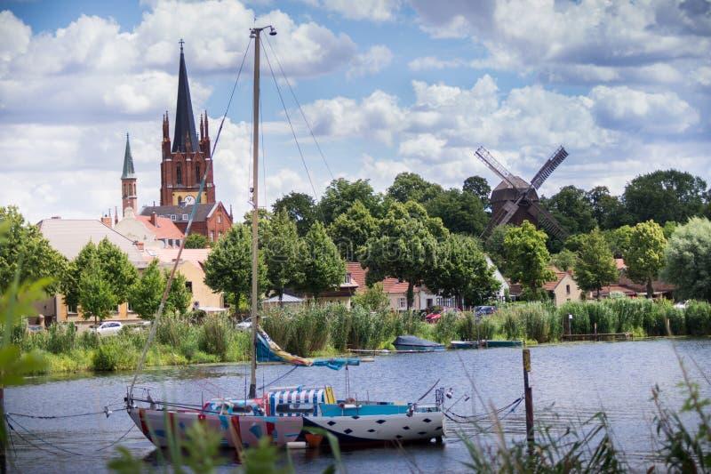 Vista del fiume con la barca e la chiesa nel fondo fotografie stock