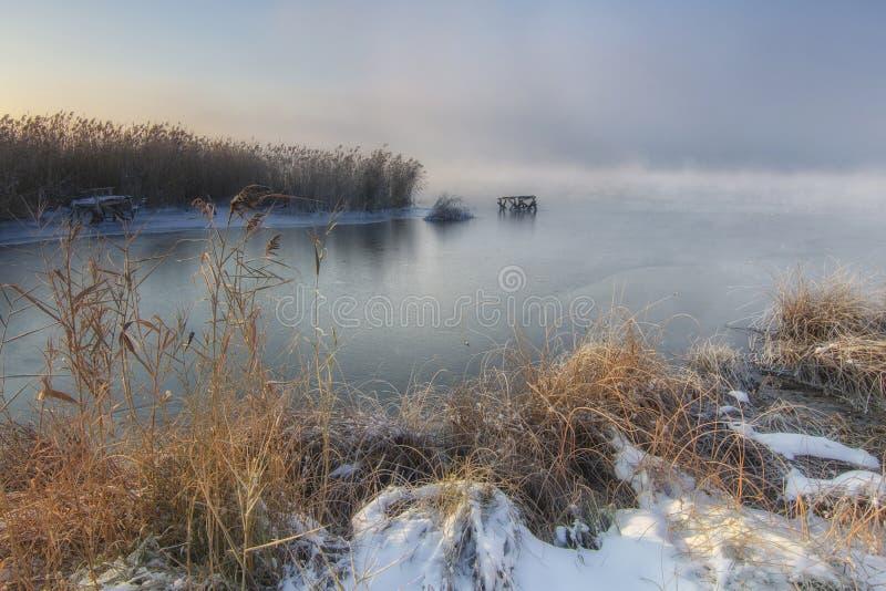 Vista del fiume congelato nella mattina nebbiosa di inverno fotografia stock libera da diritti