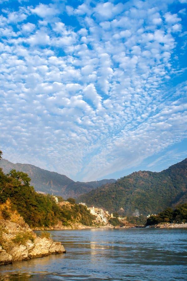 Vista del fiume Ganga e del cielo blu stupefacente con le piccole nuvole al bello giorno variopinto Rishikesh L'India fotografia stock