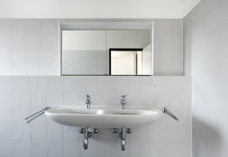 Vista del fregadero y del espejo del cuarto de baño foto de archivo