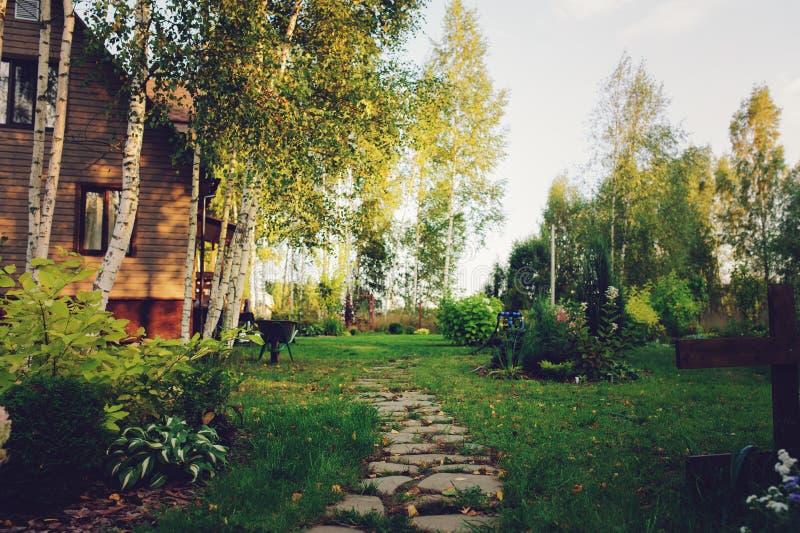 Vista del giardino del paese con la casa di legno fotografia stock