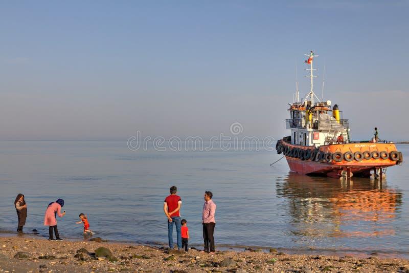 Vista del Golfo Pérsico de la tarde con ciudadanos y el barco del remolque imágenes de archivo libres de regalías